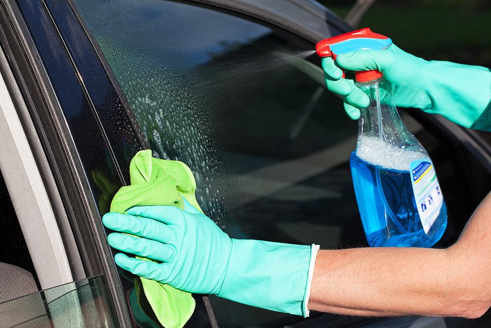 Mão feminina aplicando produto sobre a janela de um carro. Imagem ilustrativa do texto eco lavagem.