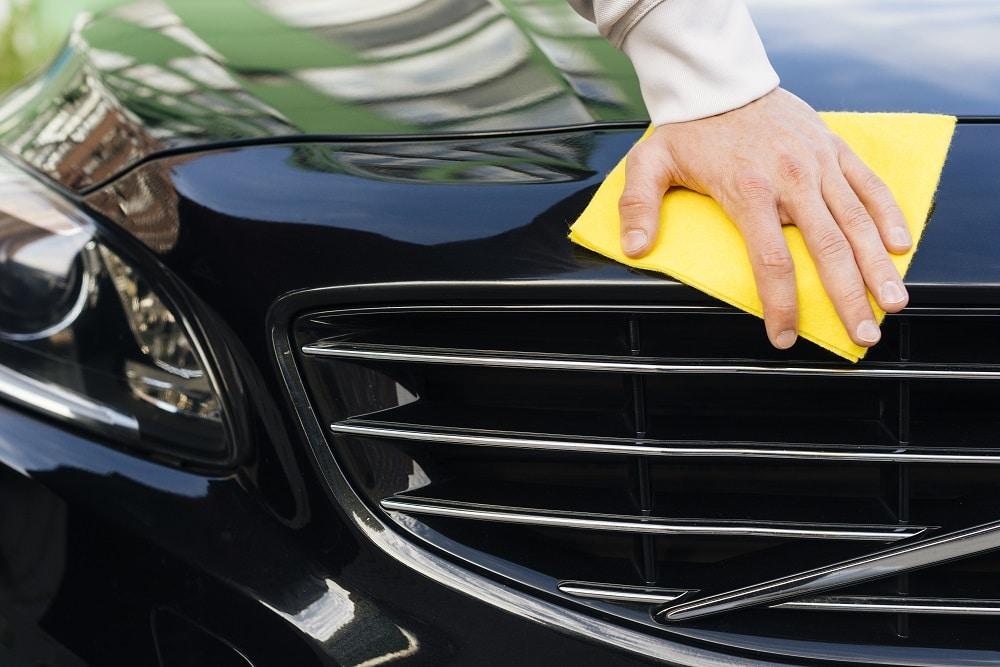 Foto da mão de uma pessoa com um pano amarelo na frente de um carro preto. Ilustração do texto sobre enceramento técnico.