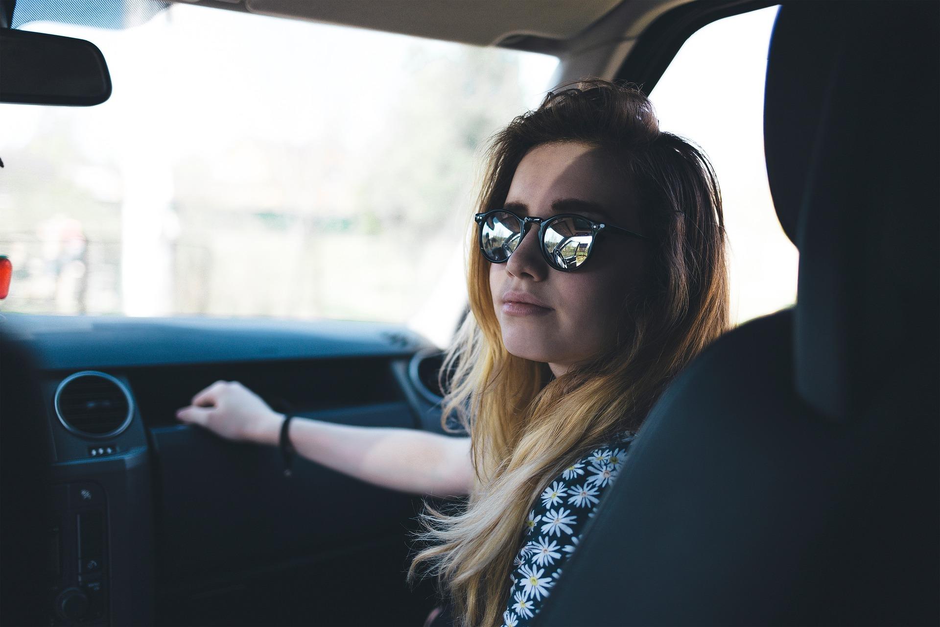 Foto de uma moça de óculos escuros, sentada no banco de passageiro do carro. Ilustração do texto sobre impermeabilização de  bancos automotivos.