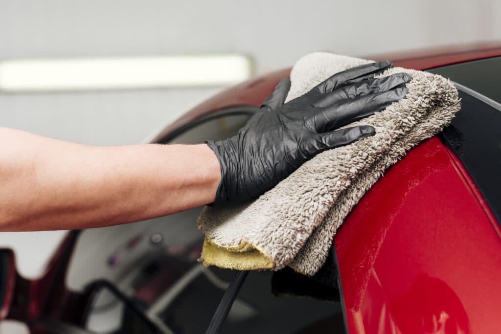 Imagem próximo do teto de um carro vermelho, enquanto uma mão com luva preta segura uma toalha cinza para fazer a limpeza. Ao fundo vemos uma parede branca. Imagem ilustrativa para o texto lava jato em Camaçari.