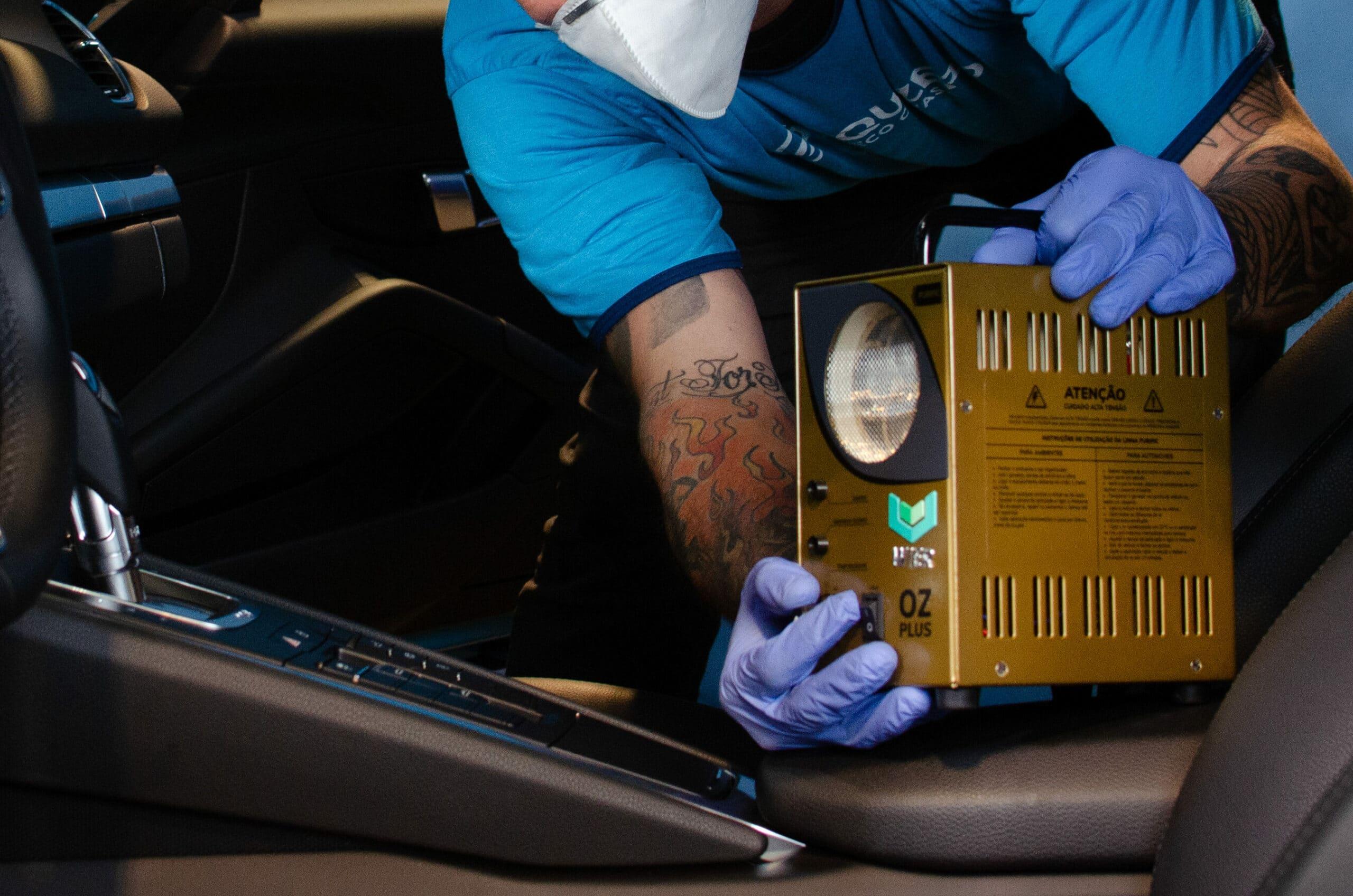 Funcionário da Acquazero com o uniforme azul da empresa segurando a máquina de gerar ozônio, dentro do interior de um carro. Imagem ilustrativa para o texto lava jato em Camaçari.