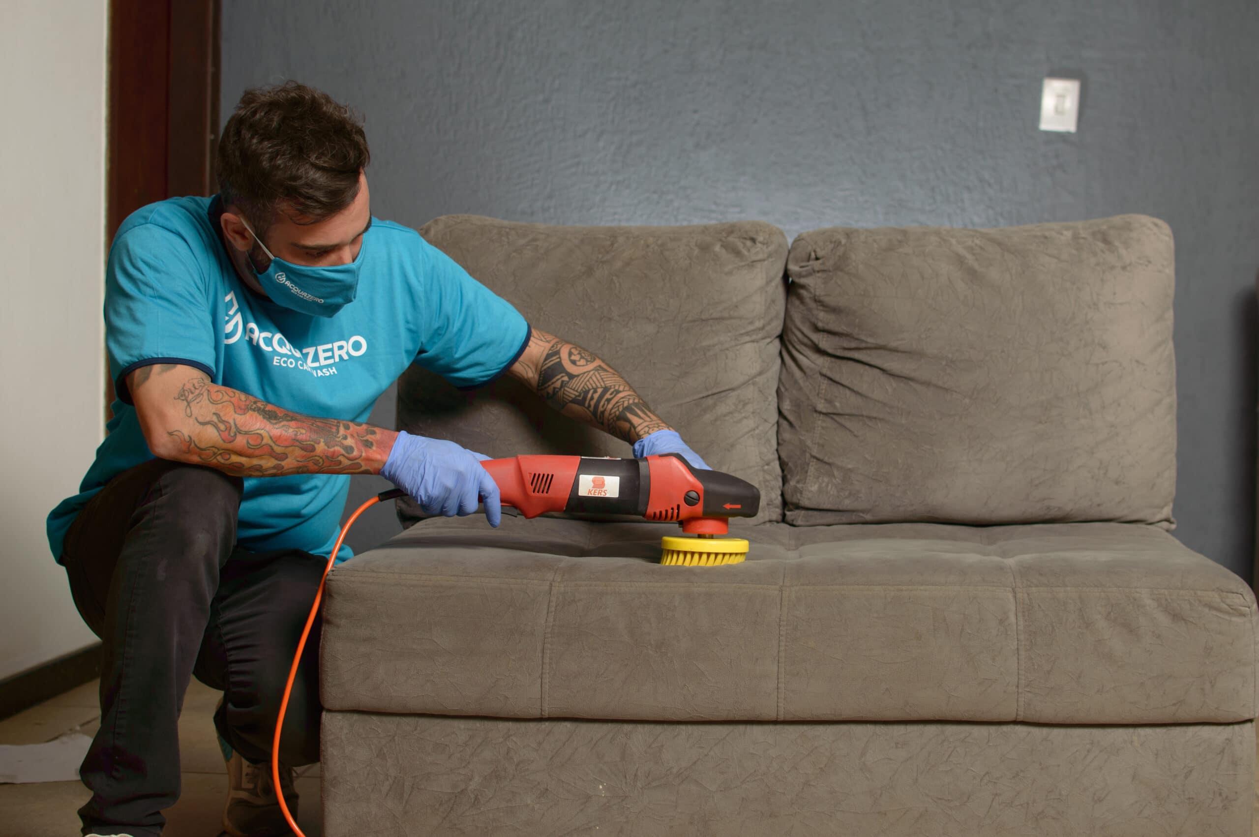 Profissional da Acquazero realiza a limpeza de um sofá cinza com o auxílio de uma escova elétrica com cerdas amarelas e cabo laranja. Ilustração do texto sobre limpeza de sofá em Macaíba.