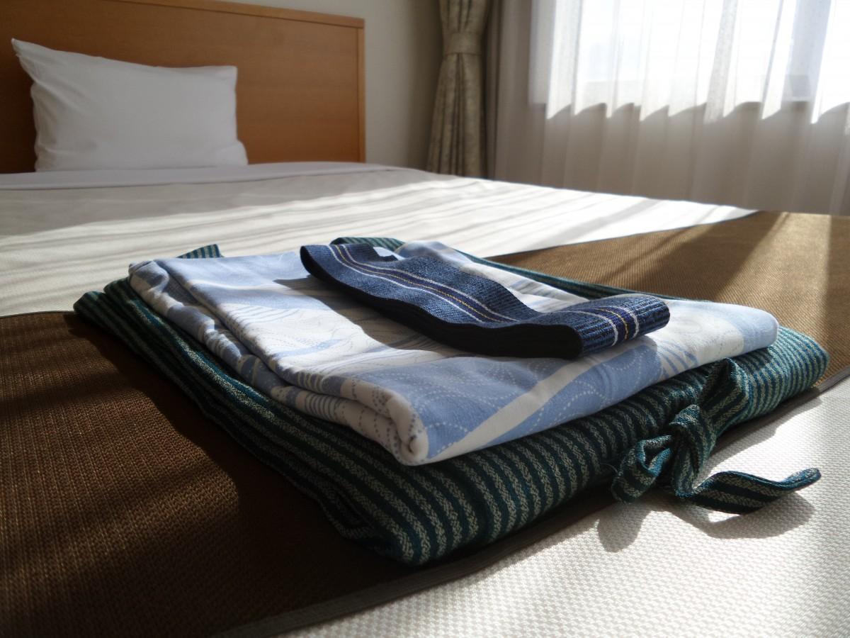 Quimono dobrado sobre a cama. Travesseiro e persiana brancos ao fundo. Imagem do conteúdo sobre limpeza de sofá em Macaíba.