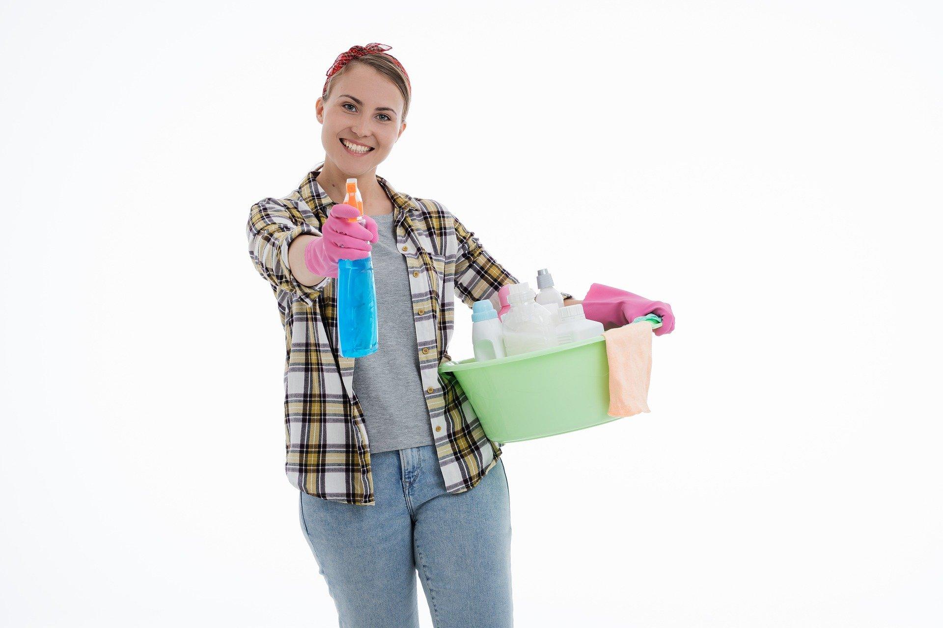 Foto de uma mulher com uma bacia e produtos de limpeza na mão. Imagem ilustrativa para o texto como remover mancha de gordura.