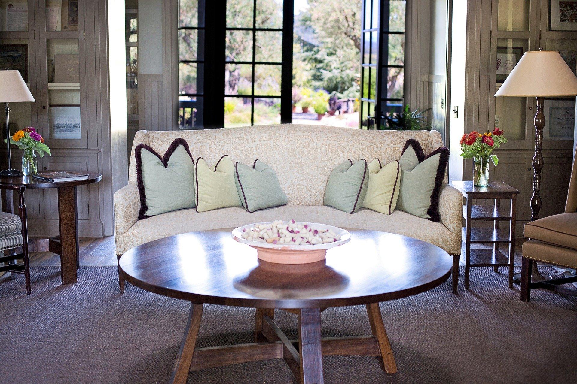 Foto de uma sala com uma mesa de centro e um sofá branco. Imagem ilustrativa para o texto como remover mancha de gordura.