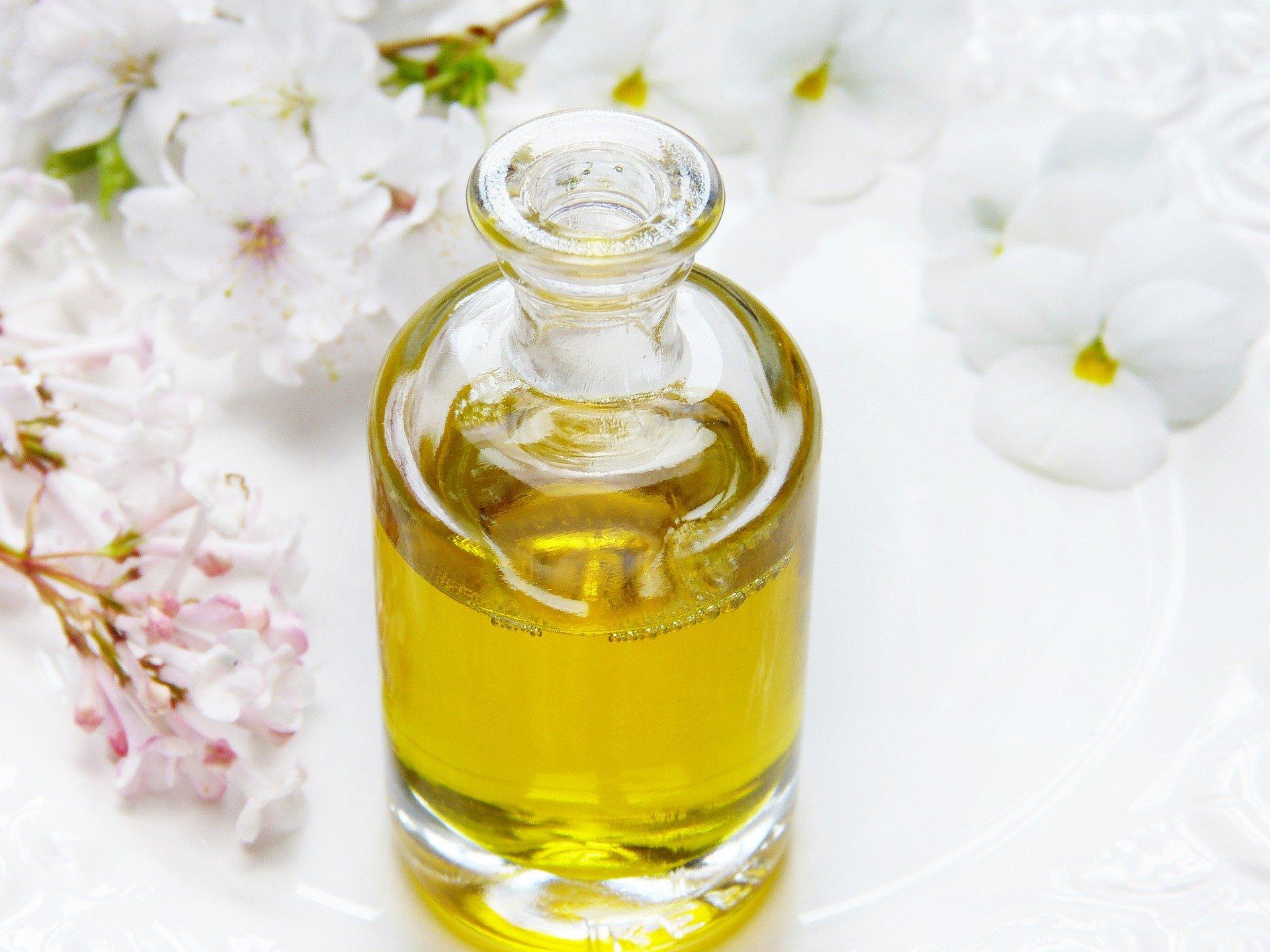 Foto de um vidro com óleo em um prato e flores ao lado. Imagem ilustrativa para o texto como remover manchas no carpete.