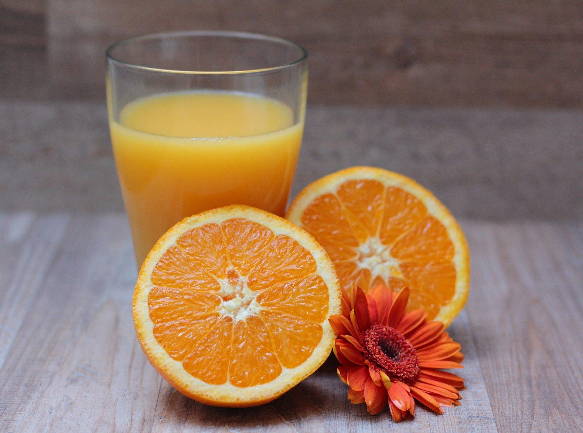 Foto de uma laranja e um copo com o suco. Imagem ilustrativa para o texto sobre como tirar mancha de fruta.