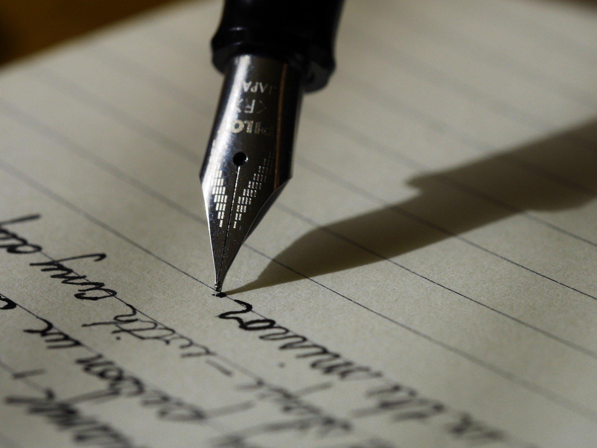 Foto de uma caneta escrevendo em um papel. Imagem ilustrativa para o texto como tirar manchas de caneta do couro.