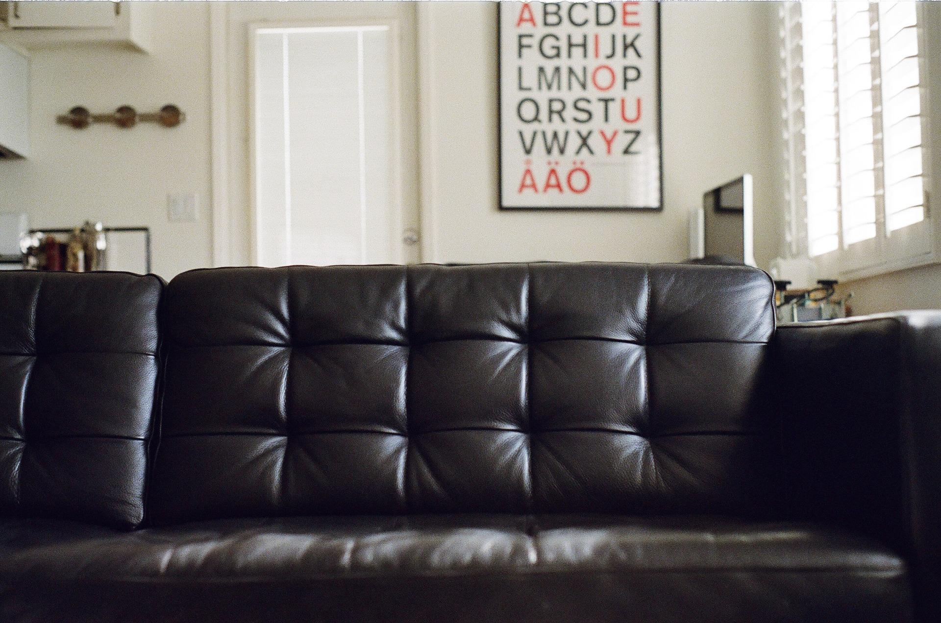 Foto de um sofá preto de couro em uma sala. Imagem ilustrativa para o texto como tirar manchas de caneta do couro.