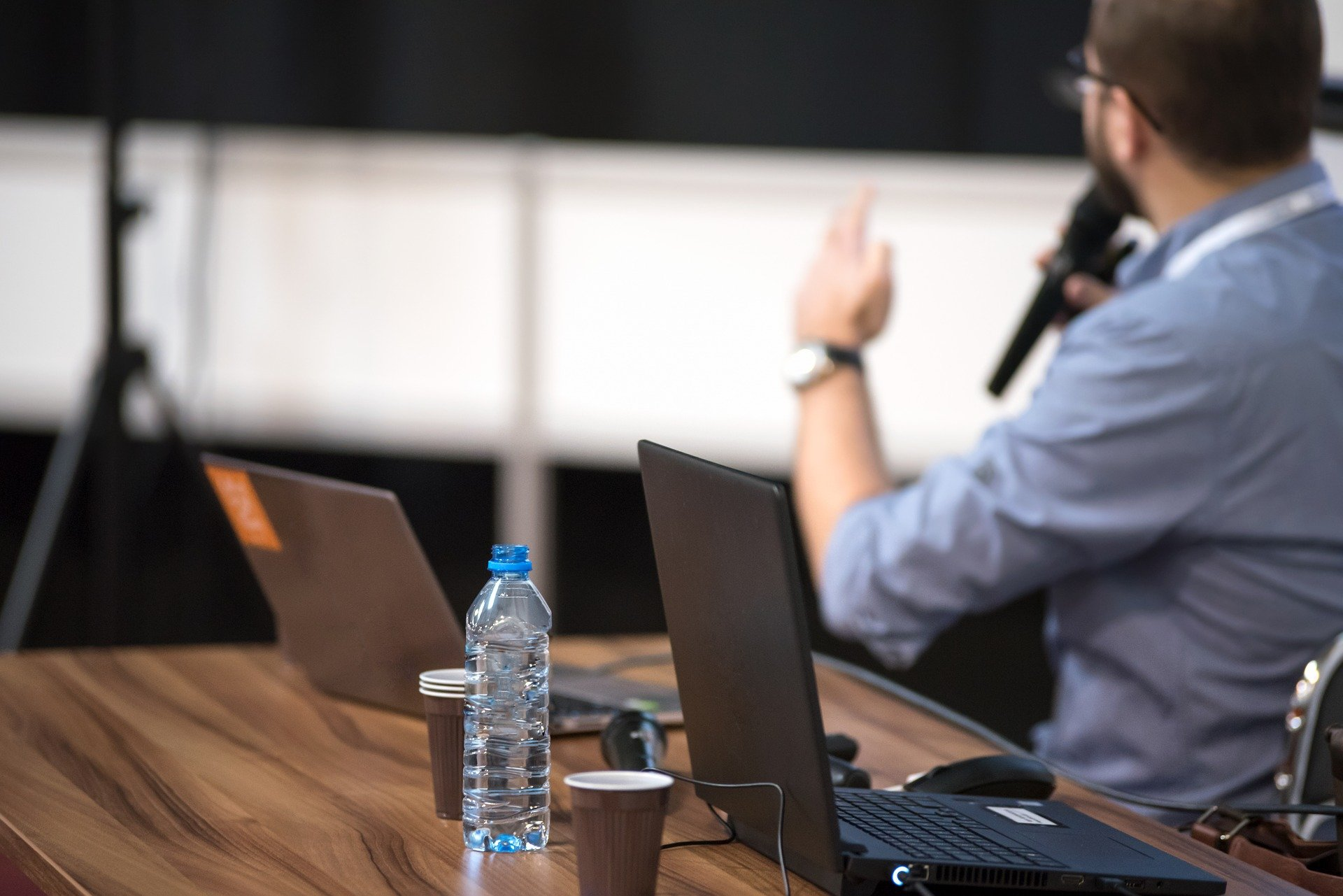 Foto de um homem apresentando em um evento com computador perto. Imagem ilustrativa para o texto feira de franquias.