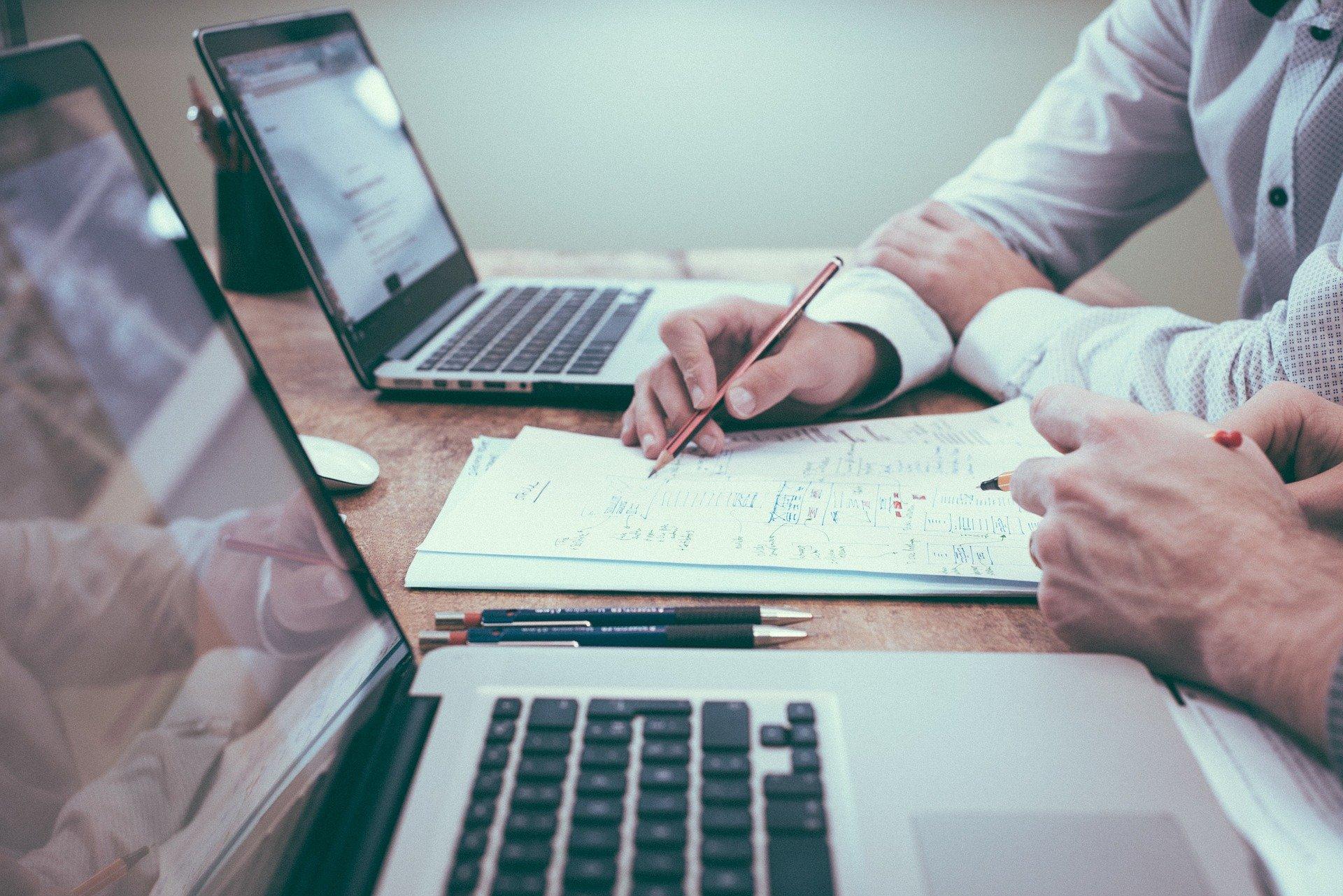 Foto de pessoas em uma mesa com papéis e anotações, ao lado de computadores. Imagem ilustrativa para o texto franquia de higienização.