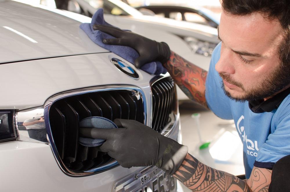 Funcionário Acquazero cuidando de um carro branco e seus detalhes. Imagem ilustrativa para o texto franquia de lava jato.