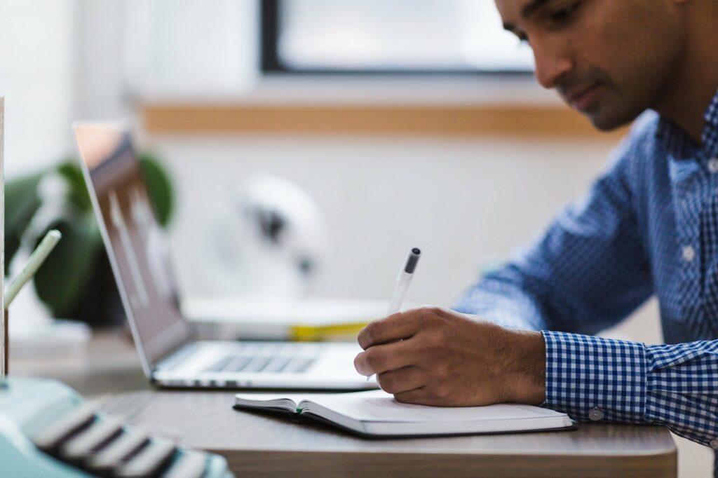 Foto de um homem fazendo anotações com computador do lado.