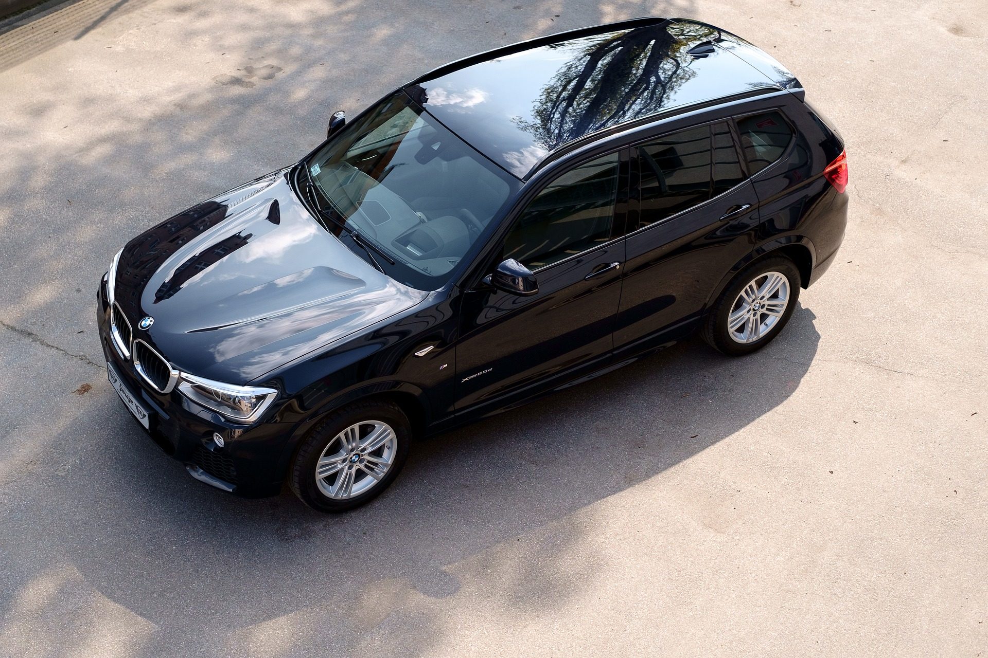 Foto de um carro preto brilhando visto do alto. Imagem ilustrativa para o texto lavar carro com pouca água.