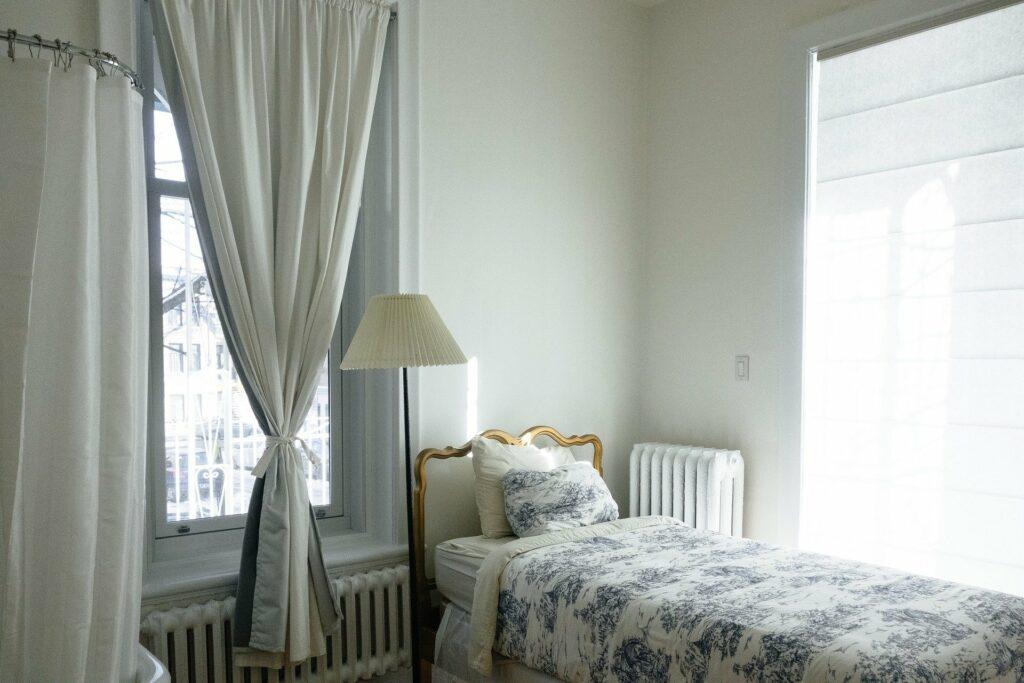 Foto de um quarto com cama e uma cortina na janela. Imagem ilustrativa para o texto lavar cortina colorida.