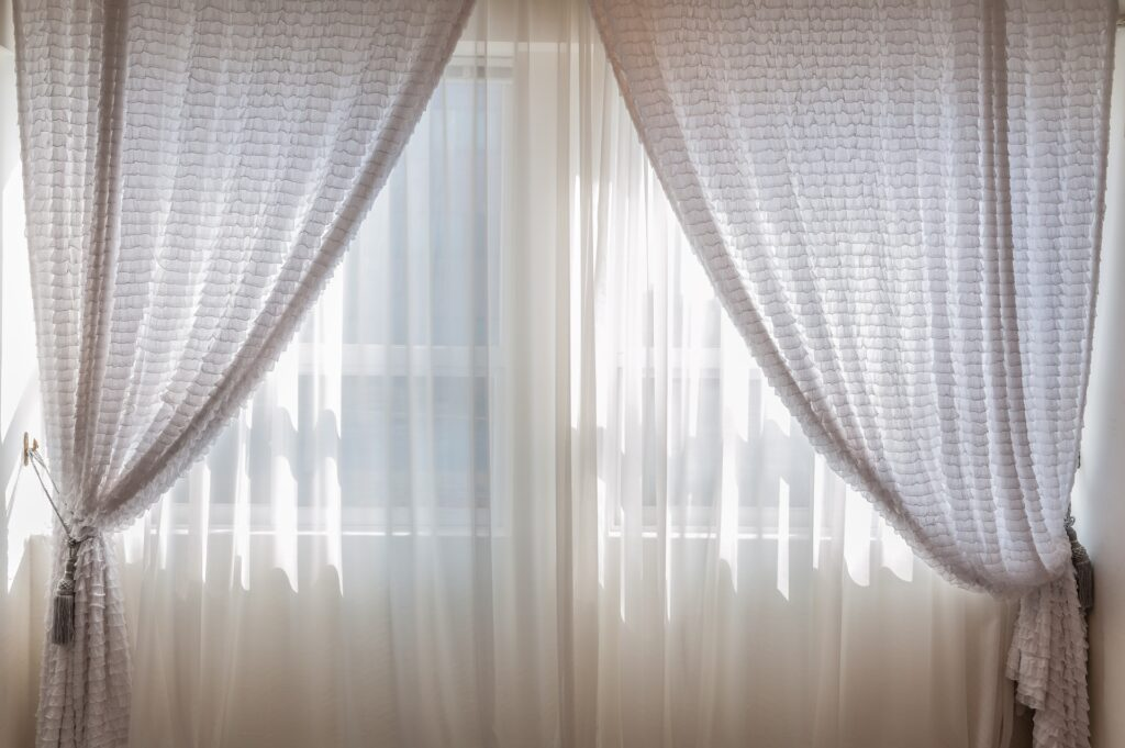 Foto de uma janela com cortinas grandes. Imagem ilustrativa para o texto lavar cortina colorida.