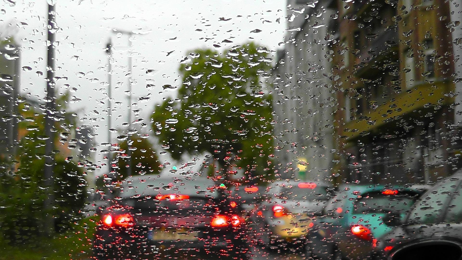 Foto da janela molhada de um carro com o trânsito do lado de fora. Imagem ilustrativa para texto limpeza de vidros.