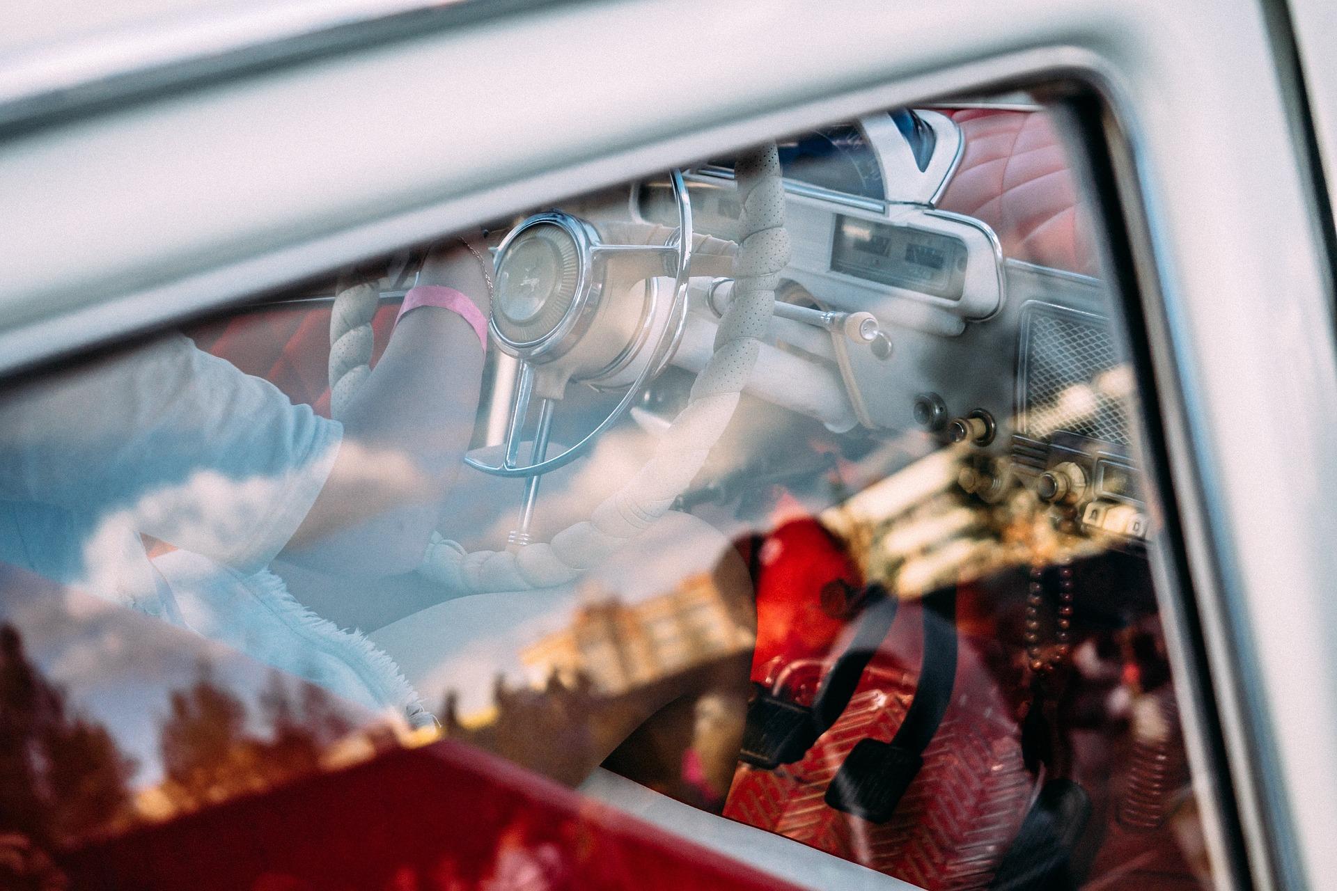 Foto da janela de um carro com uma pessoa no volante. Imagem ilustrativa para texto limpeza de vidros.