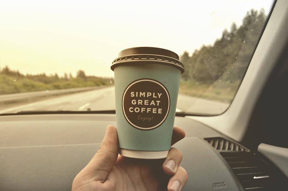 Foto de uma pessoa segurando um café dentro do carro. Imagem ilustrativa para o texto manter a higienização do carro.