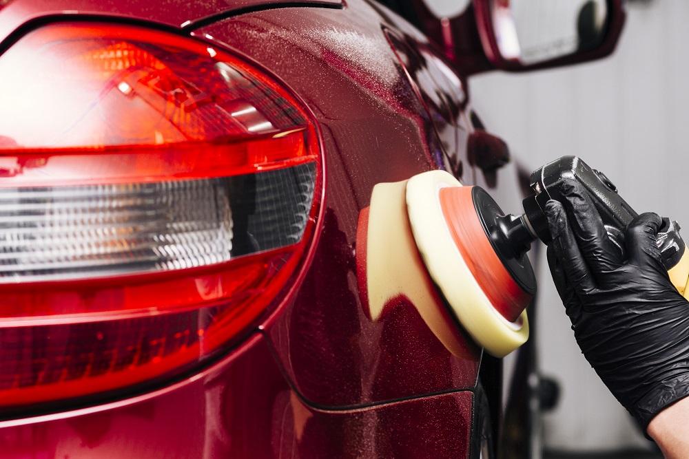 Foto de uma pessoa polindo um carro vermelho. Imagem ilustrativa para o texto quando é necessário polir o meu veículo.