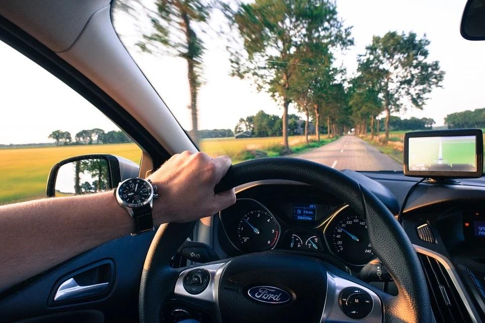 Foto de uma pessoa dirigindo carro pela estrada. Imagem ilustrativa para o texto higienização de interiores a seco.