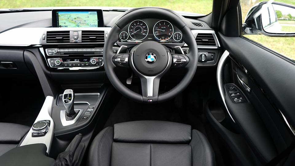 Foto da parte interna de um carro com painel e volante. Imagem ilustrativa para o texto higienização de interiores a seco.