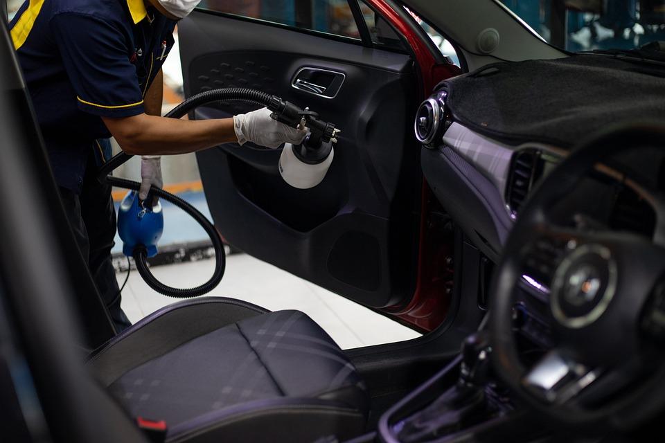 Foto de pessoa limpando carro com máquina. Imagem ilustrativa para o texto limpeza profissional de veículos.