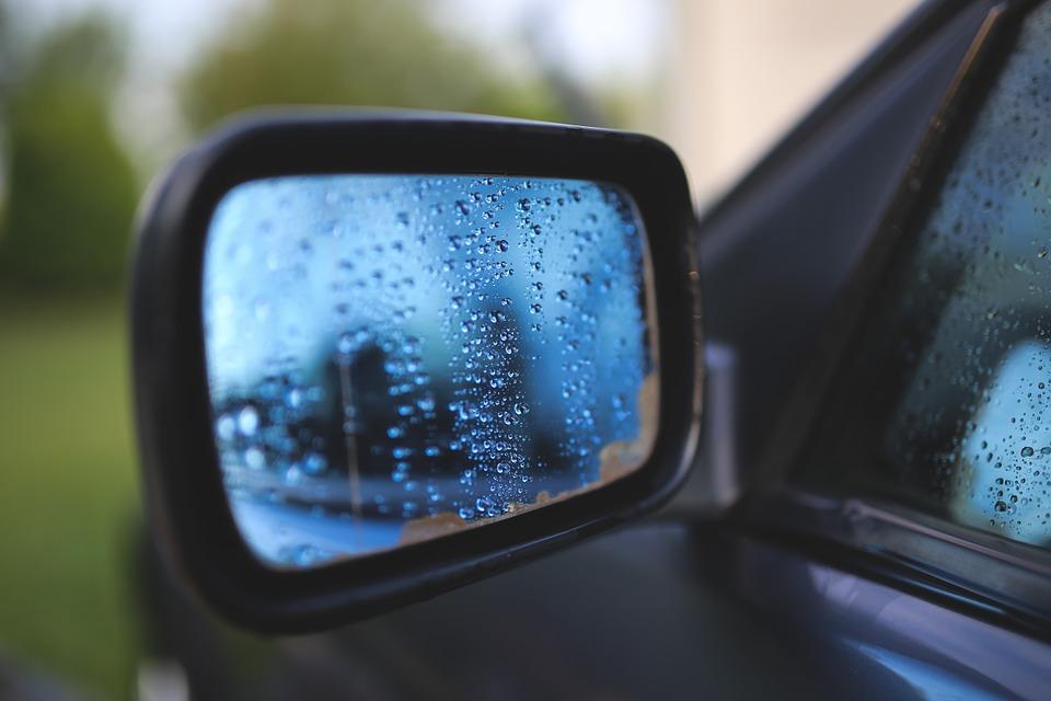Foto do retrovisor molhado de um carro. Imagem ilustrativa para o texto limpeza profissional de veículos.