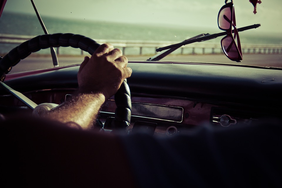 Foto de uma pessoa dentro de um veículo dirigindo. Imagem ilustrativa para o texto sanitização veicular.